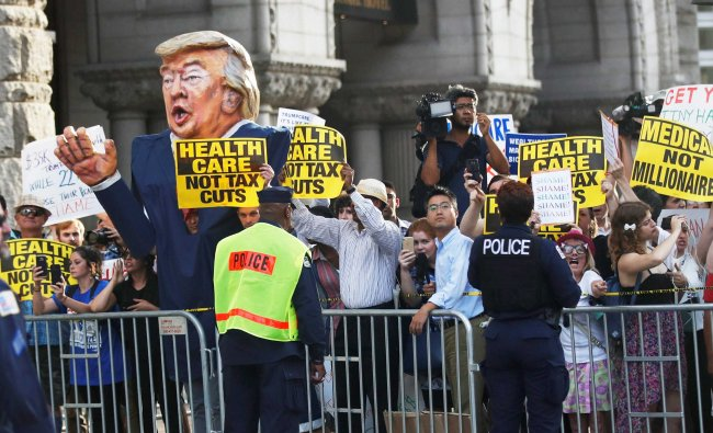 Protesters gather outside the Trump International Hotel in Washington, Wednesday, June 28, 2017...
