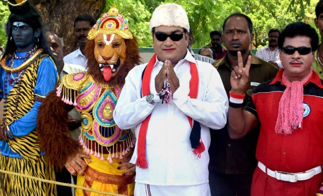 A supporter dressed up as AIADMK founder M G Ramachandran poses with others dressed up as Gods...