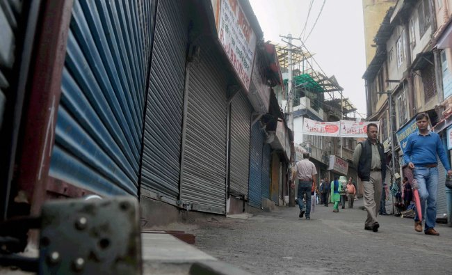 People move past closed shops during protest against Goods and Services Tax (GST) in Shimla...