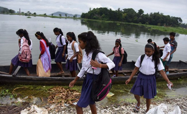 School girls travel cross a flooded area by boat at Rajbari village on the ourskirts of Guwahati...