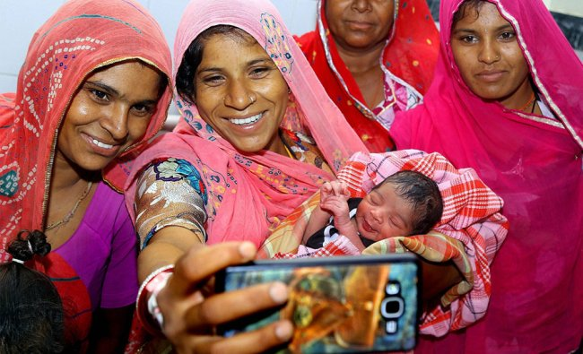 A mother takes selfies with her newborn child who was born midnight 12.02 am during the GST...