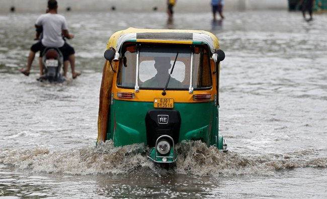 An auto-rickshaw moves through a waterlogged road after heavy rains in Ahmedabad, India...