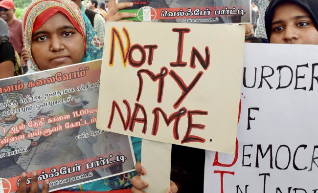 People hold placards as they participate in a protest against the targeted lynching, in Chennai...