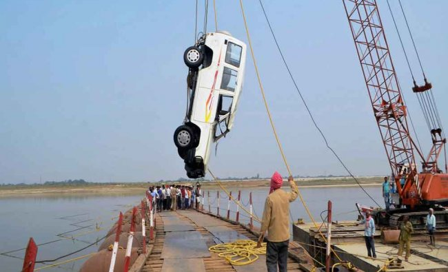A crane lifts a vehicle that fell into Ganga river from a bridge in Mirzapur...