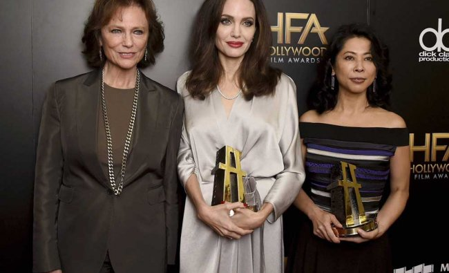 Jacqueline Bisset, left, poses in the press room with Angelina Jolie...