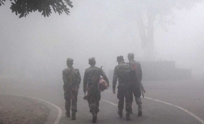 Army men walk amidst a dense fog and cold morning in Varanasi on Friday.