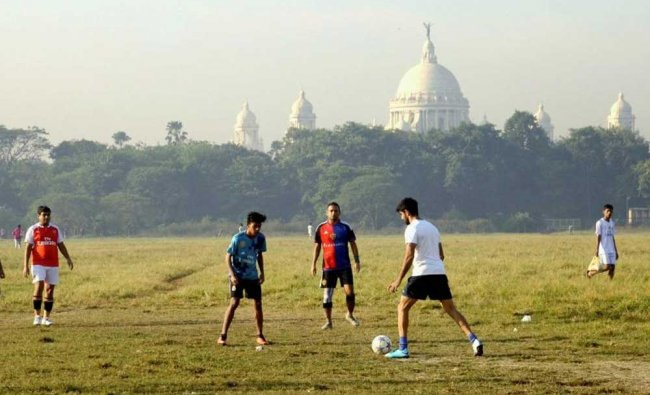 Boys seen playing football at Brigrade parade ground infront of the Victoria Memorial Hall, in ...