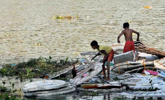 Children from a poorer neighbourhood salvage materials left after immersion of idols from various...