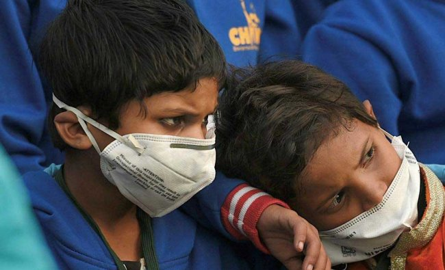 Children wearing air pollution masks attend a demonstration to spread awareness on the problem of...