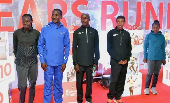 Foreign athletes pose for a group photo during a press conference ahead of the Delhi Half Marathon.