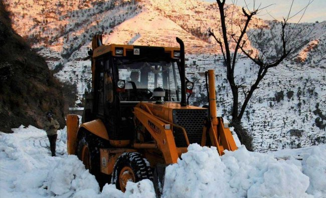 A snow cutter machine clears the road after heavy snowfall at Peer Ki Gali in Poonch...