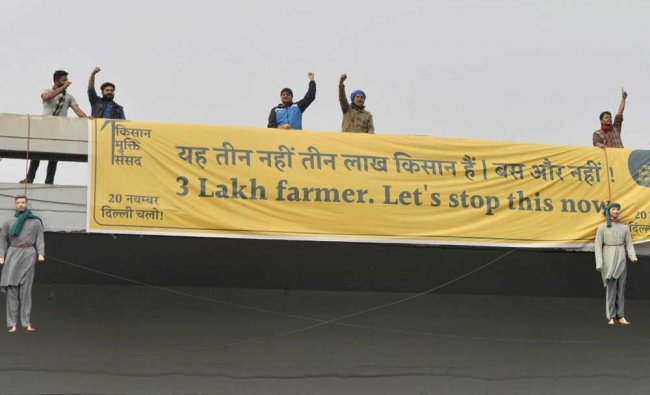Activists of the Kisan Mukti Sansad hanging dummy bodies of farmers from a flyover during a...