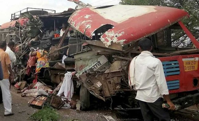 People watch an ill fated bus after an accident which killed many people in Latur...
