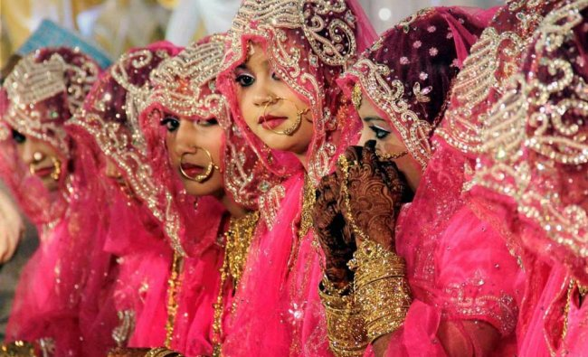 Brides sit for a mass marriage ceremony organized for 12 Muslim couples at Mazgaon...