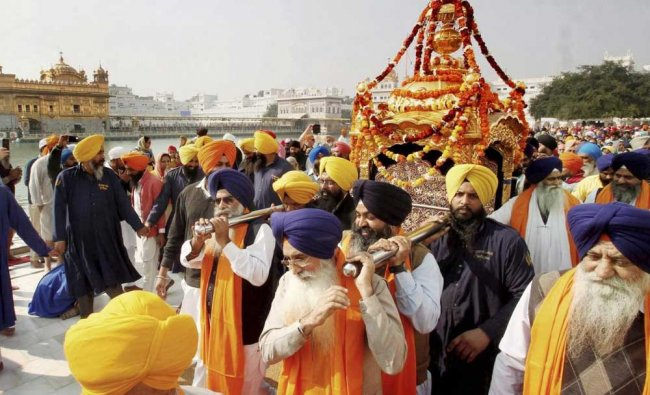 Sikh devotees carrying palanquin in a Nagar Kirtan procession at the Golden Temple...
