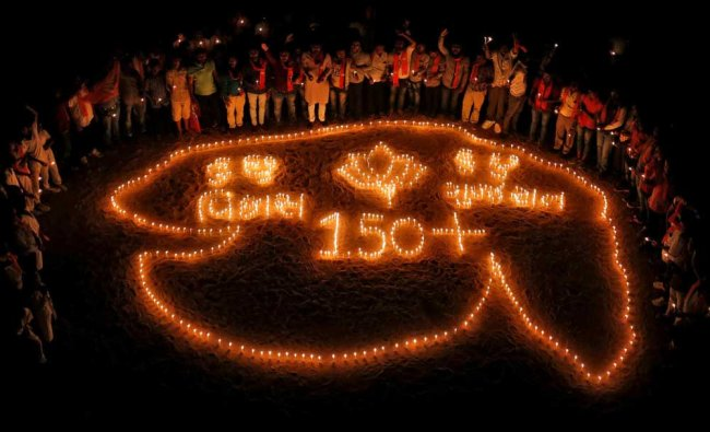 BJP supporters pose after lighting candles in a formation of the map of Gujarat...