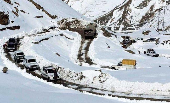 Vehicles moving at snow clad road after snowfall in Lahau...