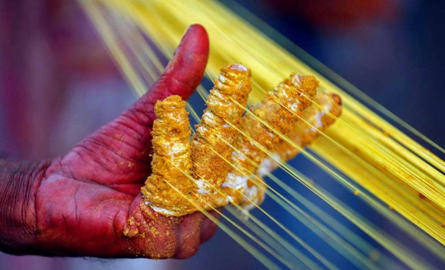 A worker applies colour to strings which will be used to fly kites, by a roadside in Ahmedabad...
