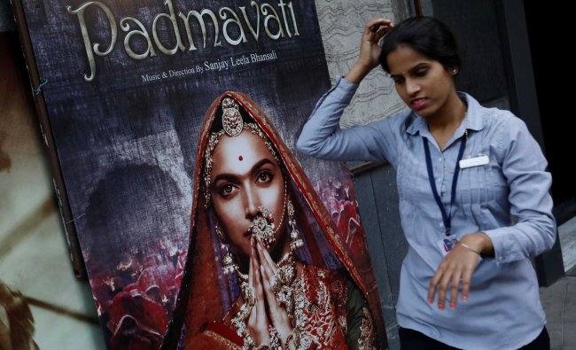 An employee walks past a poster of the upcoming Bollywood movie \'Padmavati\' outside a theatre...