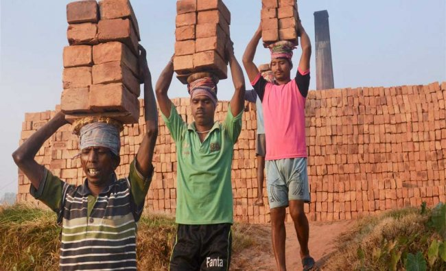 Labourers carry bricks on their head during loading at a brick field on the banks of river...
