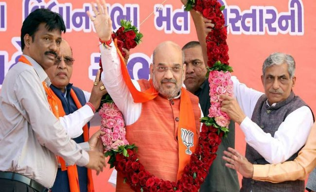 BJP National President Amit Shah waves at a public meeting in Vagra assembly constituency...