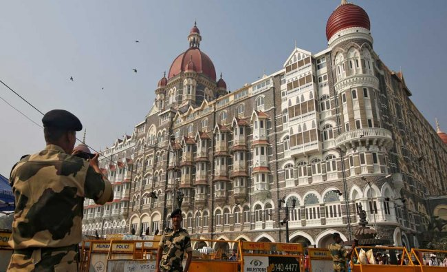 A BSF soldier takes photographs of his colleague in front of Taj Mahal hotel, which was...