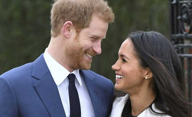 Britain\'s Prince Harry and Meghan Markle smile as they pose for the media in the grounds...