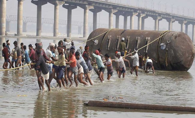 Labourers construct a temporary pontoon bridge over the River Ganges ahead of the \'Magh Mela\'...