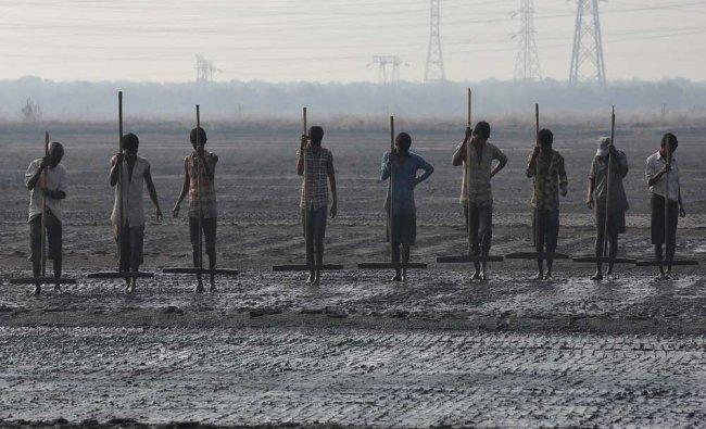 Workers level a salt pan in Mumbai, India. Reuters...