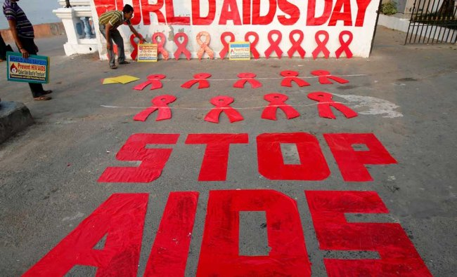 A man places a placard as he prepares a message during an HIV/AIDS awareness campaign...
