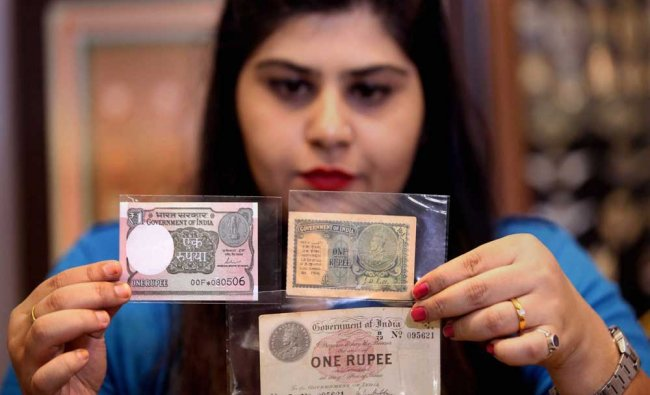 A woman showing one of the first 1 rupee notes, launched 100 years ago...