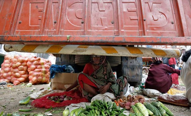 A woman selling vegetables waits for customers under a parked supply truck at a wholesale market...