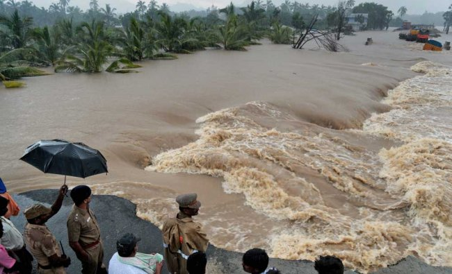 People watrch a washed-away road in Suchindram...