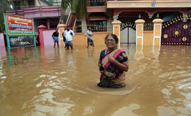 A woman wades through a waded street in Suchindram...