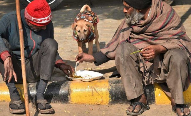 Homeless people sharing meal at a pavement in New Delhi...
