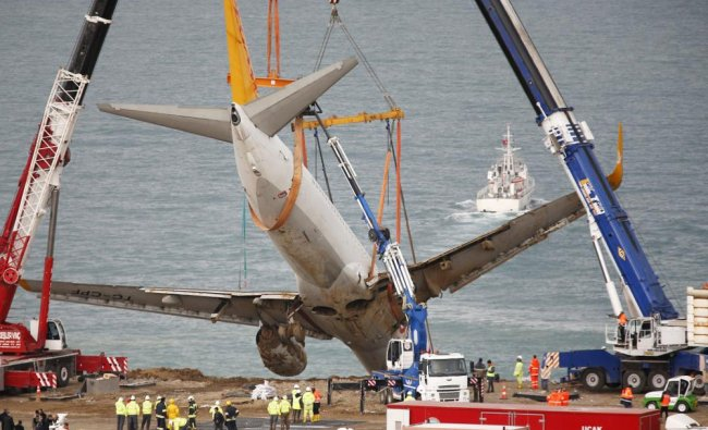 Cranes lift a Boeing 737-800 of Turkey\'s Pegasus Airlines in Trabzon, Turkey...