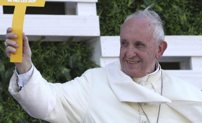 Pope Francis holds a cross that reads in Spanish \