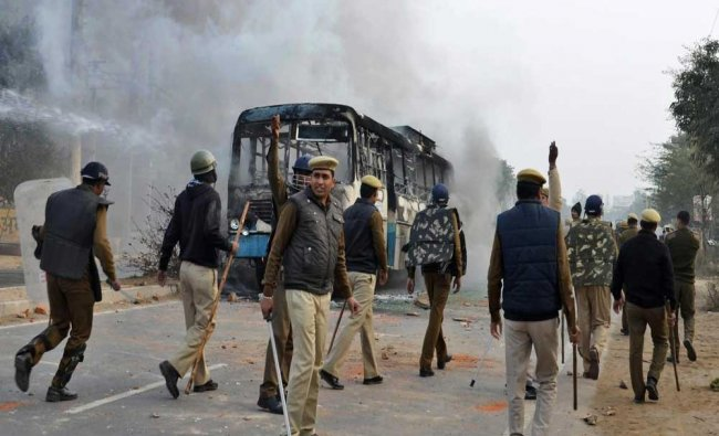 Firefighters and police try to douse a fire after alleged activists of the Karni Sena torched...