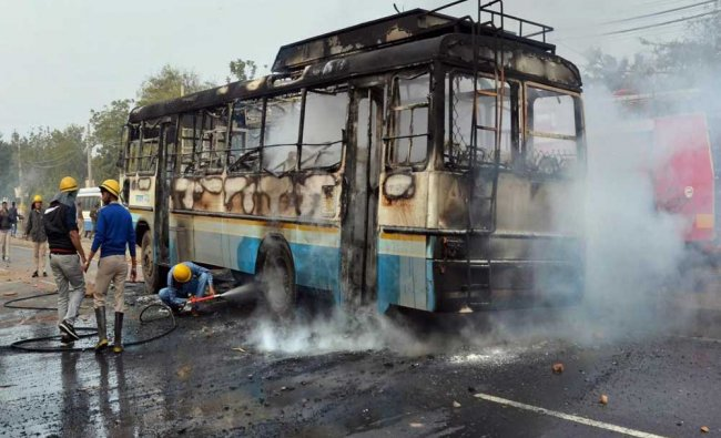 Firefighters try to douse a fire after alleged activists of the Karni Sena torched a Haryana...