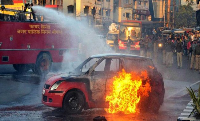 A firefighter tries to douse flames after Karni Sena activists torched a car during...
