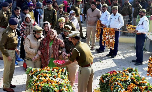 Police personnel console a relative as she pays her last respects to the policeman who was killed ..