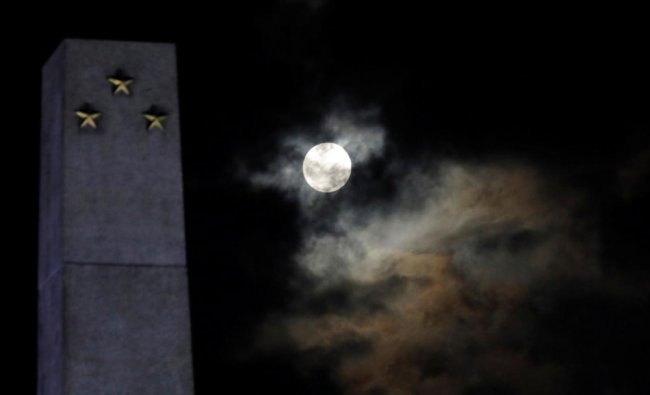 A full moon is seen before the lunar eclipse at Rizal Park, metro Manila, Philippines ...