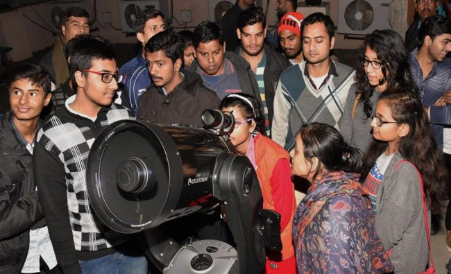 A woman looks through a telescope to see the super blue blood moon\' a rare lunar eclipse from the..