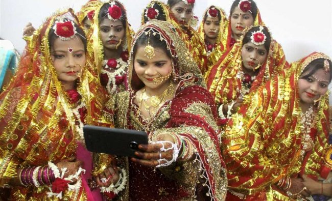 Differently abled brides take a selfie during a mass marriage ceremony, in Allahabad...
