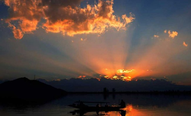 A fisherman with his family rows his boat during sunset in Dal Lake, Srinagar...