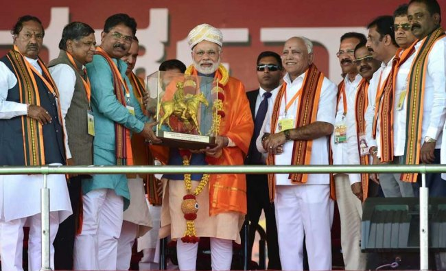 PM Modi being presented a memento by BJP leaders during the completion of the Parivartan Yatra rally