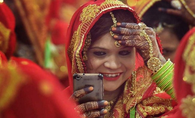 A bride adjusts her headgear looking into her phone during community mass wedding ceremony in.