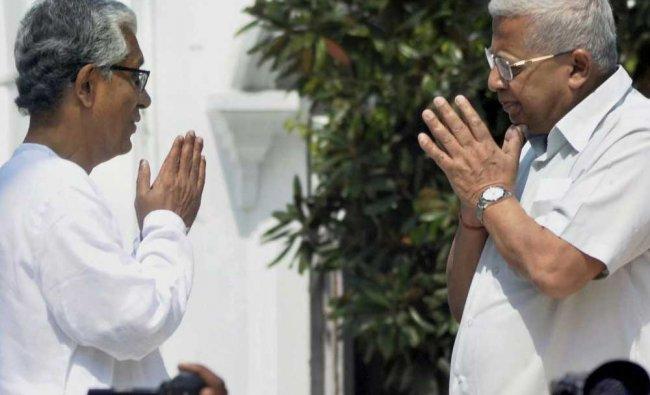 Tripura chief minister Manik Sarkar greets Tripura Governor Tathagata Roy after submitting his...