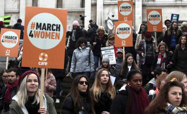 Protestors hold placards as they demonstrate during the March4Women event in central London, Britain