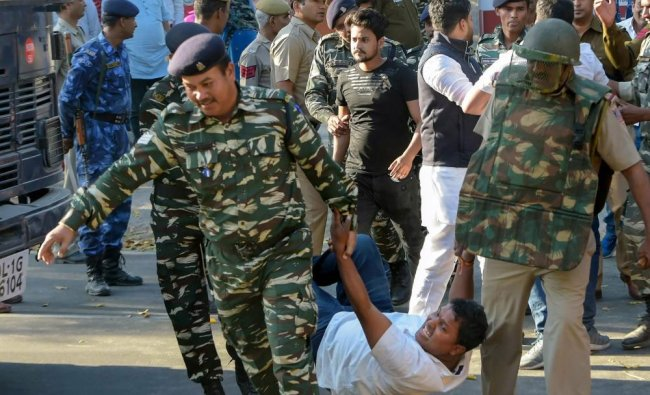 CRP personnel take away Indian Youth Congress activists during a demonstration against BJP ...